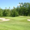 A view of a green protected by a collection of bunkers at Sodus Bay Heights Golf Club