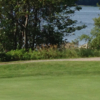 A view of a green with water in background at Thousand Islands Country Club